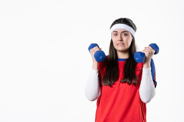 Vista frontale confusa giovane donna in abiti sportivi con manubri blu