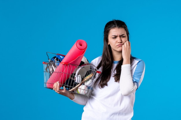 Front view confused young female with basket after sport shopping