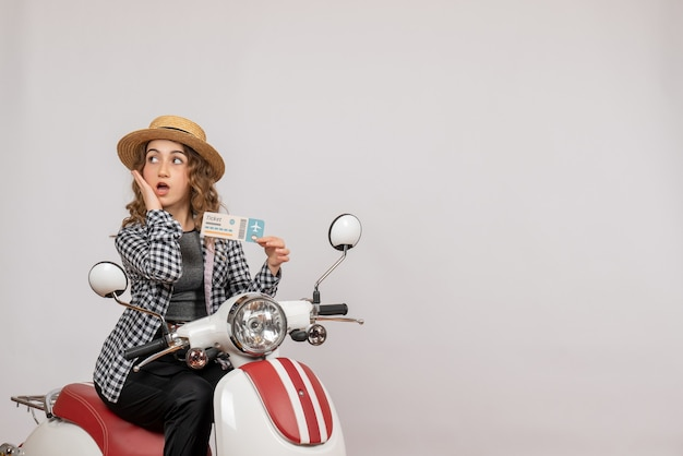 Front view of confused young girl on moped holding up clipboard on grey wall