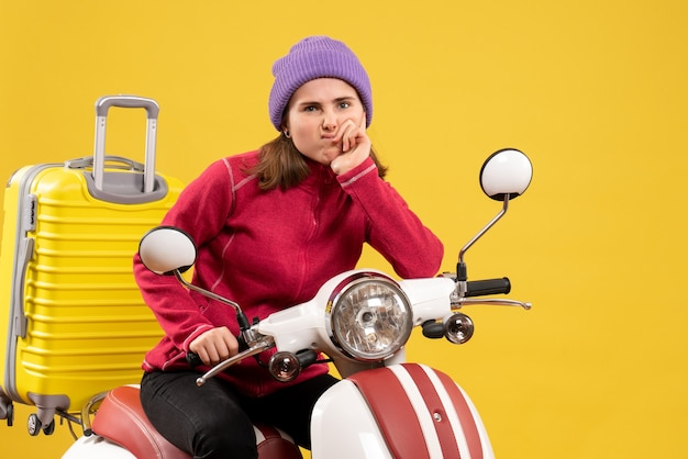 Vista frontale ragazza confusa sul ciclomotore con la valigia gialla