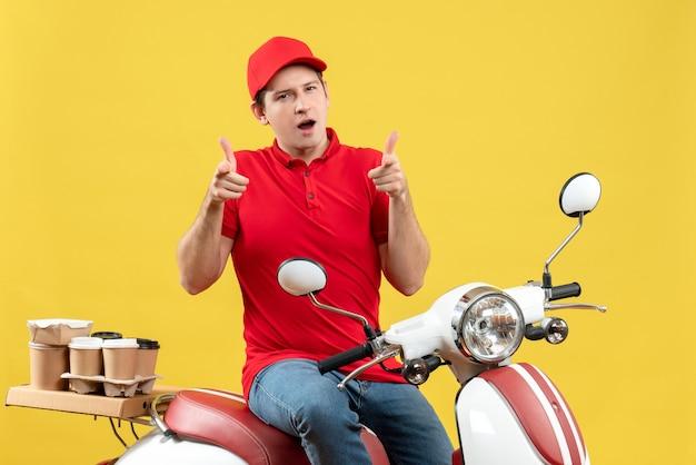 Vista frontale del giovane ragazzo confuso che indossa camicetta rossa e cappello che consegna gli ordini che puntano in avanti su sfondo giallo