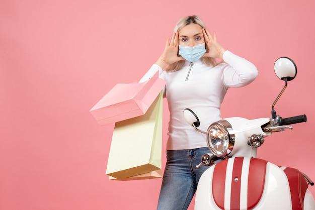 Vista frontale confusa giovane signora che tiene i sacchetti della spesa vicino al ciclomotore