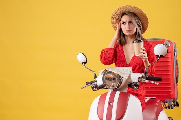Vista frontale della giovane signora confusa in vestito rosso che tiene la tazza di caffè vicino al ciclomotore