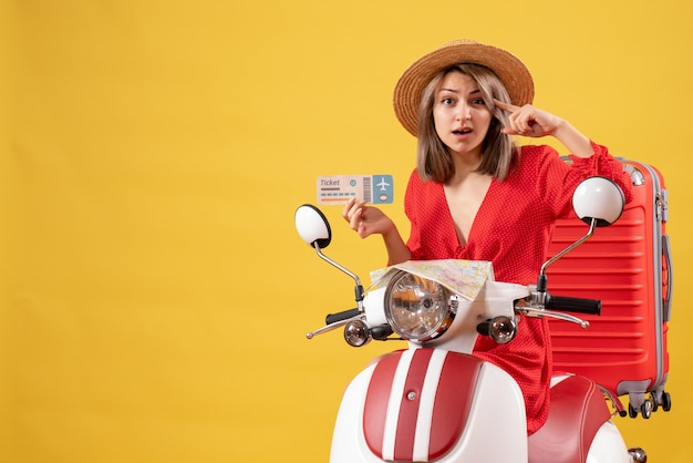 Vista frontale della giovane donna confusa in vestito rosso che sostiene il biglietto aereo sul ciclomotore