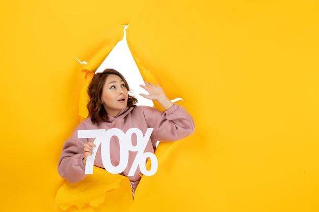 Vista frontale della giovane donna confusa che mostra il segno del settanta percentuale e guarda in alto sul giallo strappato