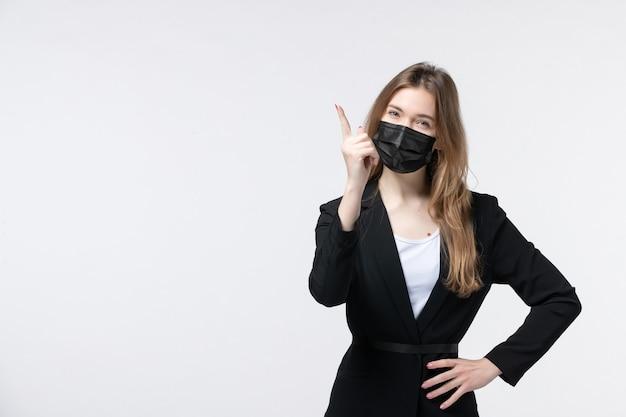 Vista frontale della giovane donna confusa in tuta che indossa maschera chirurgica e punta verso l'alto su bianco