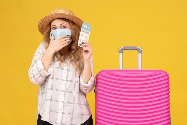 Vista frontale della giovane donna confusa che indossa la maschera che mostra il biglietto e in piedi vicino alla sua borsa rosa su giallo