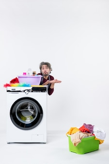 Front view confused young man in apron sitting behind washer laundry basket on white background