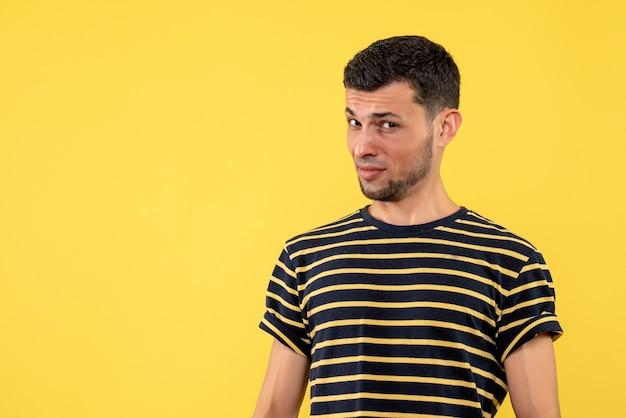 Вид спереди смущенный молодой человек в черно-белой полосатой футболке на желтом изолированном фоне с копией пространства
