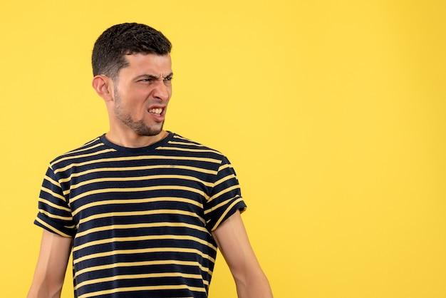 Вид спереди смущенный молодой человек в черно-белой полосатой футболке на желтом изолированном фоне