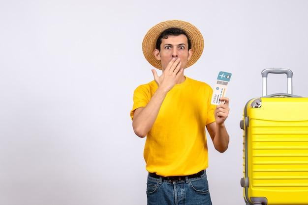 正面図黄色のスーツケースの近くに立っている黄色のtシャツと麦わら帽子で混乱した若い男
