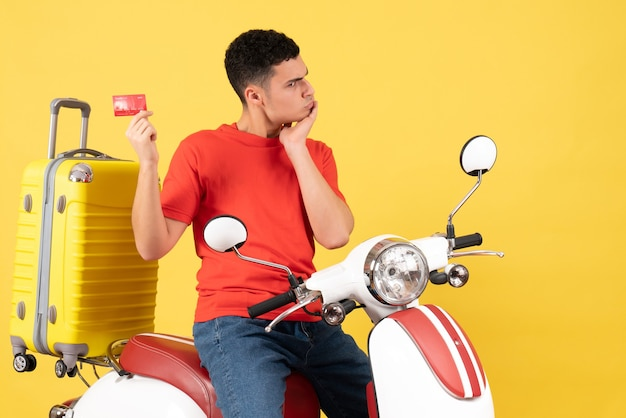 Вид спереди смущенный молодой человек на мопеде с банковской картой
