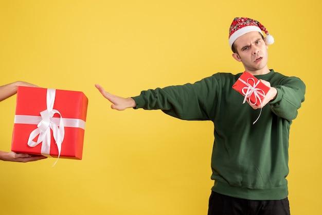 Vista frontale confuso giovane uomo che rifiuta il dono in mano femminile su giallo