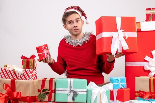 전면보기 혼란 스 러 워 크리스마스 선물 주위에 앉아 젊은 남자
