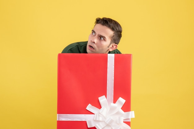 Front view confused young man standing behind big giftbox on yellow