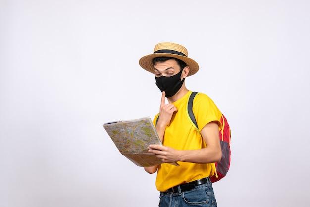 Vista frontale confuso giovane con maschera e zaino rosso guardando la mappa