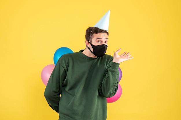 正面図は黄色の上に立っているパーティーキャップとカラフルな風船で若い男を混乱させた