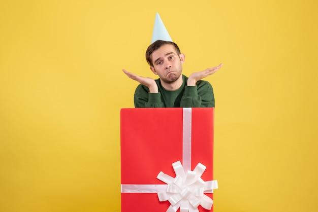 Giovane uomo confuso di vista frontale con il cappuccio del partito che sta dietro il grande giftbox su giallo