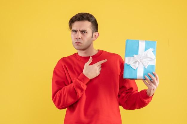 Вид спереди смущенный молодой человек с красным свитером, стоящий на желтом фоне