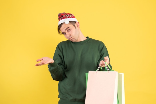 Front view confused young man with santa hat holding shopping bags standing on yellow