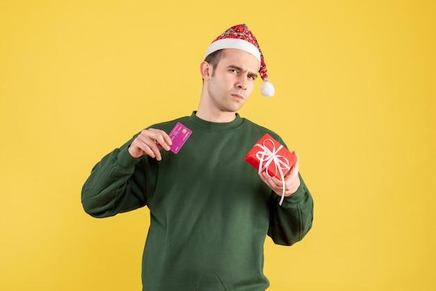 Вид спереди смущенный молодой человек с рождественским подарком, стоящий на желтом