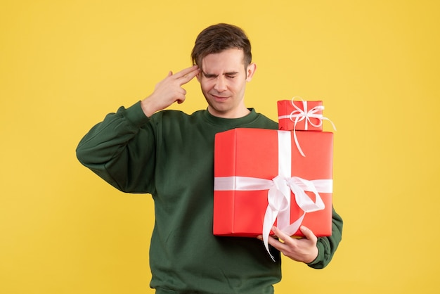 Front view confused young man with xmas gift standing on yellow