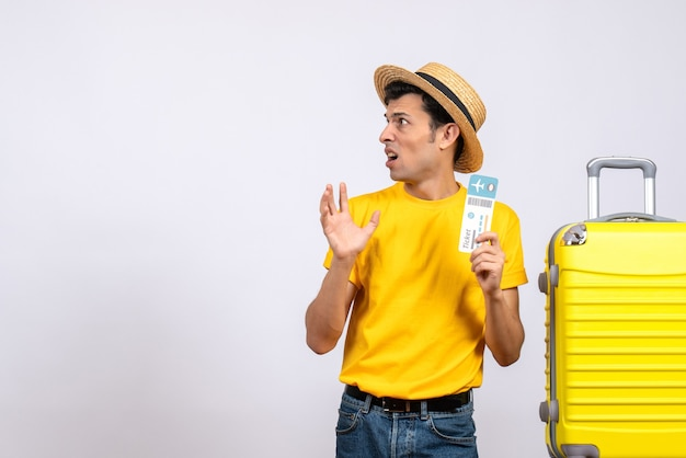 Front view confused young man in yellow t-shirt standing near yellow suitcase holding ticket