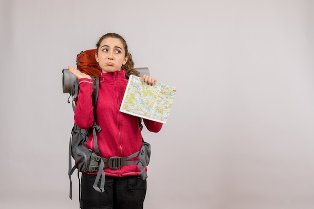 Front view of confused young traveller with big backpack holding up map on grey wall
