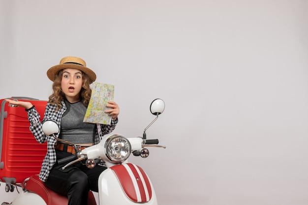 Vista frontale della giovane donna confusa sulla mappa della holding del ciclomotore sul muro grigio