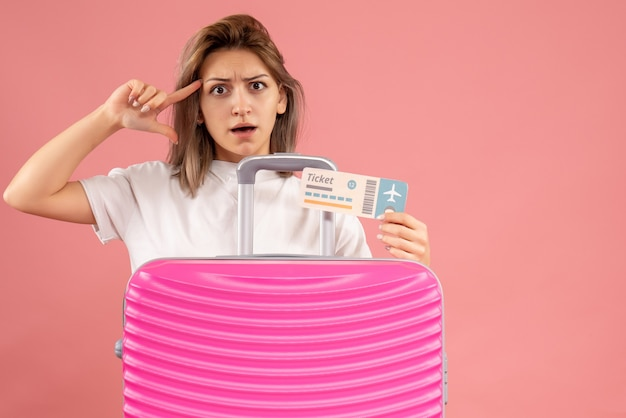 Vista frontale della giovane donna confusa con il biglietto rosa della tenuta della valigia