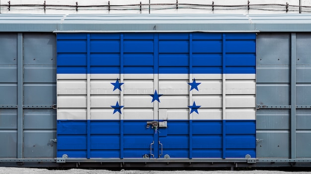 Front view of a container train freight car with a large metal lock with the national flag of honduras. the concept of export and import, transportation, national delivery of goods