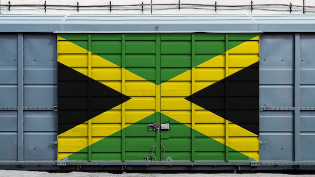 Front view of a container train freight car with a large metal lock with the national flag of jamaica.the concept of export - import, transportation, national delivery of goods and rail transportation