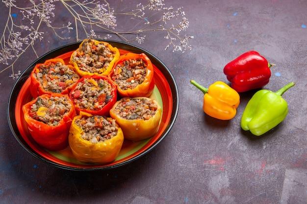Vista frontale cotti peperoni con carne macinata su una superficie grigia dolma carne di manzo cibo verdure carne