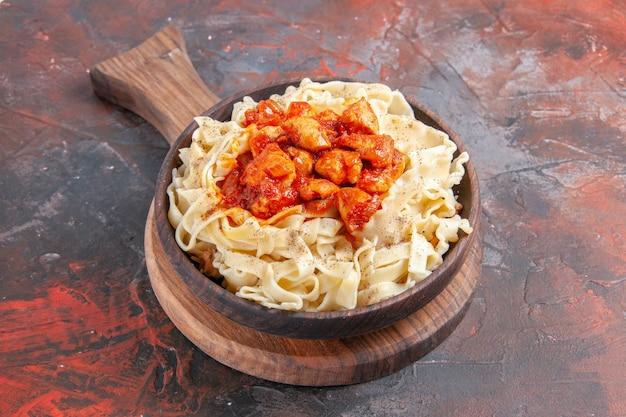 正面図暗い表面のパスタ生地の暗い皿に鶏肉とソースで調理された生地