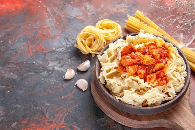 チキンと調味料を使った正面図の調理済み生地を暗い表面のパスタ皿生地に