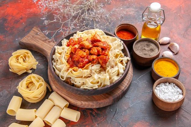 Vista frontale pasta cotta con pollo e condimenti su pasta piatto superficie scura pasta scura