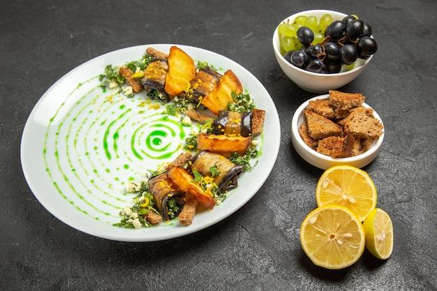 正面図暗い背景の皿の夕食の食事の果物の料理のブドウおよびレモンのスライスが付いている調理されたナスのロール