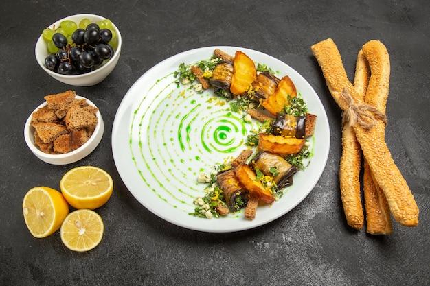 正面図暗い背景の皿の夕食の食事の果物の料理のブドウとレモンのスライスと調理されたナスのロール