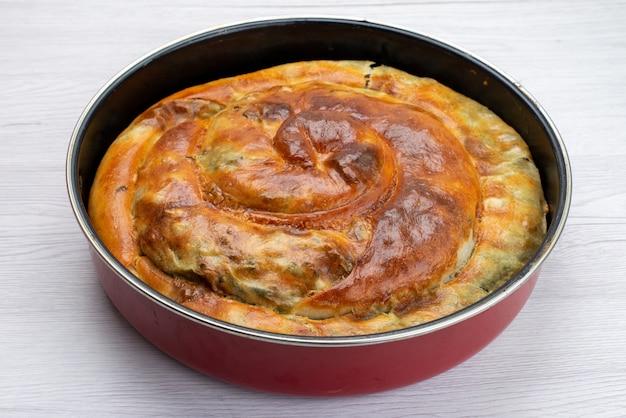 Vista frontale della torta di verdure cotte all'interno della padella rotonda sulla superficie bianca