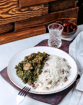 Front view cooked greens rice along with beans inside white plate on the white surface