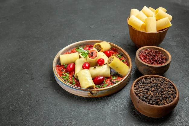 正面図調理されたイタリアンパスタトマトソースとグレーの背景に調味料を使ったおいしい食事生地パスタミートフードソース