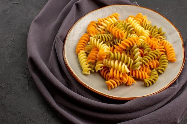 Vista frontale pasta italiana cucinata pasta a spirale insolita all'interno del piatto sullo spazio buio Foto Gratuite
