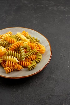 Front view cooked italian pasta unusual spiral pasta inside plate on the dark space