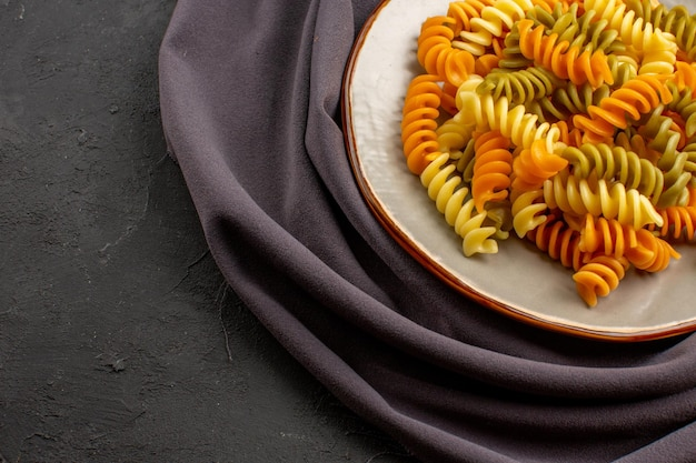 Вид спереди приготовленные итальянские макароны необычные спиральные макароны внутри тарелки на темном пространстве