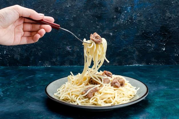 正面図調理されたイタリアンパスタとスライスした肉が青い表面で食べられるパスタイタリア料理ディナー生地肉