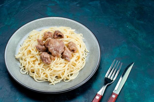 正面図調理されたイタリアンパスタ、青い表面のプレートの内側にスライスした肉パスタイタリア料理ディナー生地肉