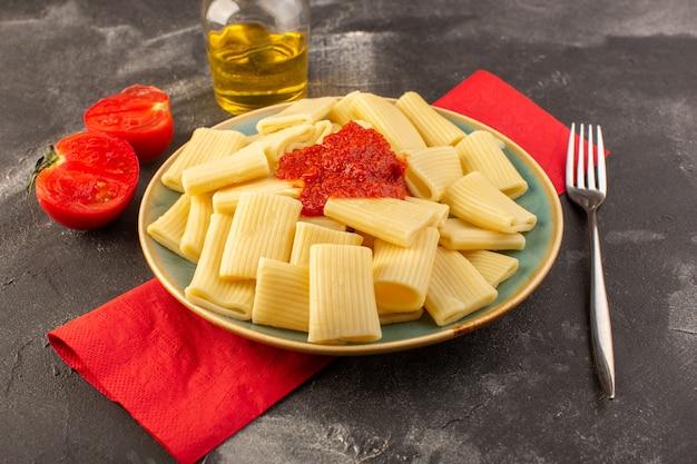 Una vista frontale ha cucinato la pasta italiana con salsa di pomodoro all'interno del piatto sul pasto di cibo italiano di pasta da tavola grigia