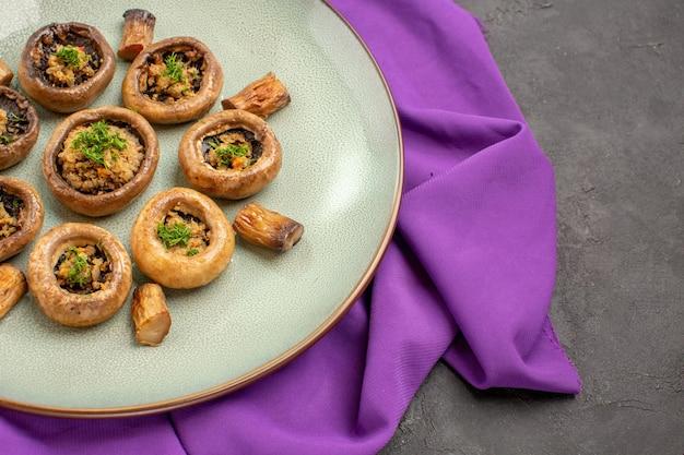 Вид спереди приготовленные грибы внутри тарелки на фиолетовой ткани и на темном фоне блюдо, приготовление ужина с грибами