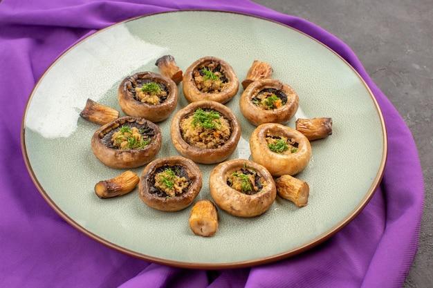 Vista frontale funghi cotti all'interno del piatto su un piatto di tessuto viola funghi cottura della cena