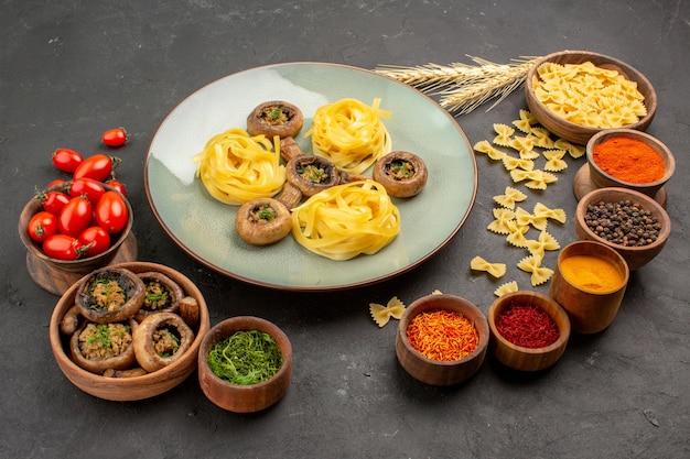 Вид спереди приготовленные грибы с приправами на темном столе